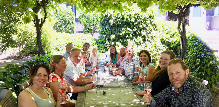 Group enjoying lunch under the vines in the sunken terrace at Black BarnPicture